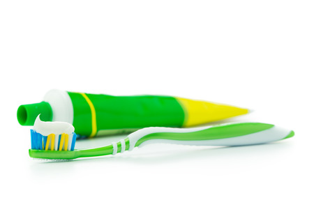 Tube of toothpaste and green toothbrush over white background Stock Photo