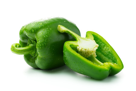 Green bell peppers with water droplets on white background