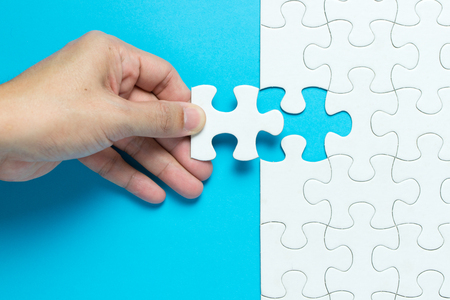 Hand put the last piece of jigsaw puzzle to complete the mission Stok Fotoğraf