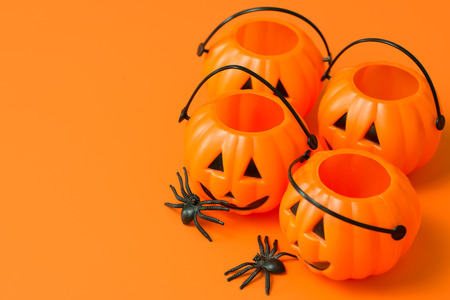 Halloween pumpkin buckets and spiders on orange background, with copy space