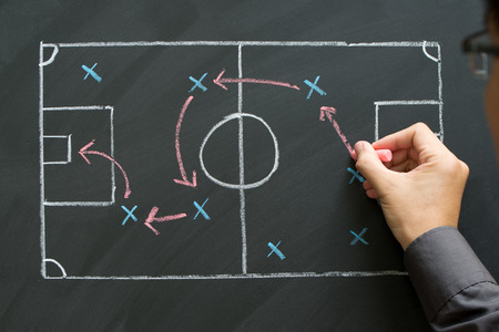 Man planning for a football strategy on blackboard Stock Photo