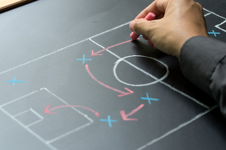 schemes: Man planning for a football strategy on blackboard Stock Photo