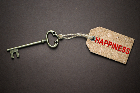 The key of happiness isolated over black background