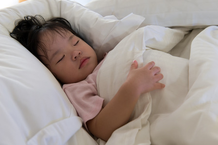 Close up of little Asian child sleeping sound on bed