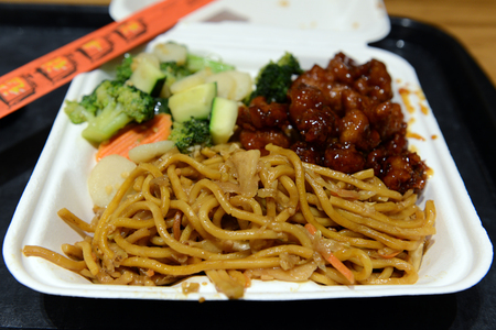 Close up of stir fly noodles, served with broccoli and meat, packed in styrofoam container.