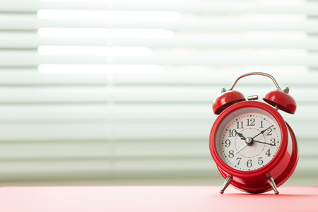 Red alarm clock with morning sunlight from white blinds