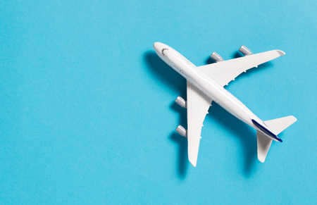 Miniature airplane isolated on blue background, with copy space