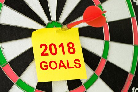 Setting 2018 goals concept using the sticky note and dart