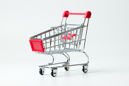 Miniature empty red color shopping cart or trolley isolated on white background