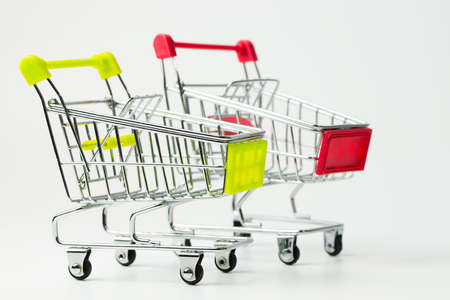 Miniature empty red and yellow color shopping carts or trolley isolated on white background