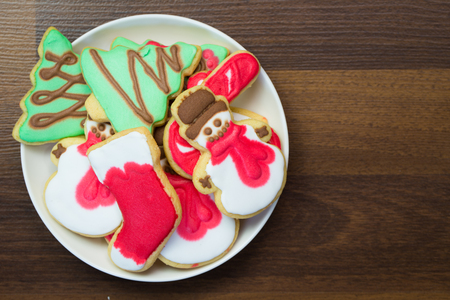 homemade christmas cookies decorated with royal icing served in white plate flat lay stock photo