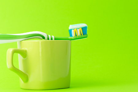 Toothbrush with toothpaste and green mug isolated on apple green background