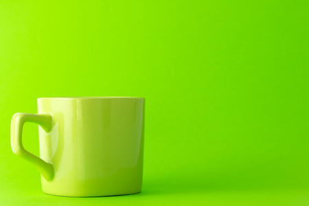 Empty apple green cup isolated on green background Foto de archivo