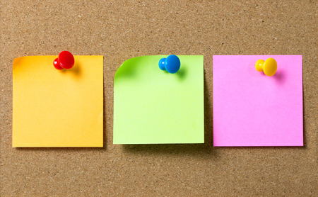 Three colors sticky notes paper attached to cork board using thumb tack pin Archivio Fotografico