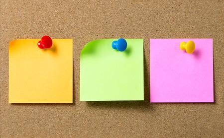 Papier à notes autocollantes de trois couleurs fixé au panneau de liège à l'aide d'une épingle à punaise Banque d'images