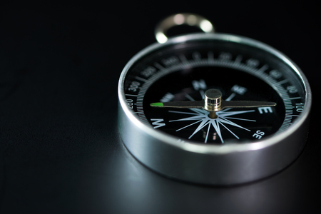 Classic magnetic compass isolated in dark background