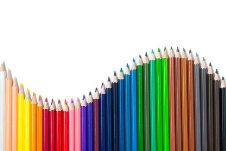 De kleurenpotloden van het spectrum geplaatst die in S-kromme worden geschikt die op witte achtergrond wordt geïsoleerd
