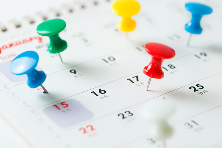 Various color thumb tack pins on calendar as reminder