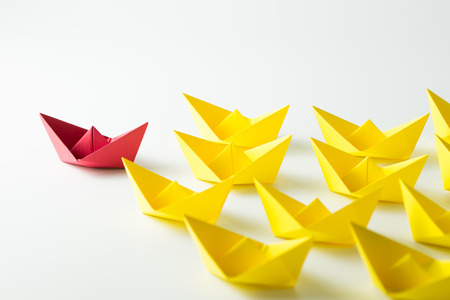 Leadership concept with a red paper ship leading among yelllow ships Banque d'images