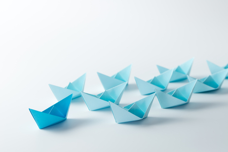 Leadership concept with a dark blue paper ship leading among light blue ships Stock Photo