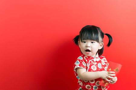Little Asian girl holding red envelope on red background
