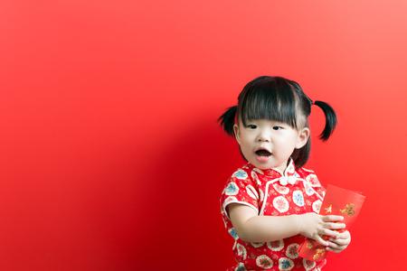 Little Asian girl holding red envelope on red background