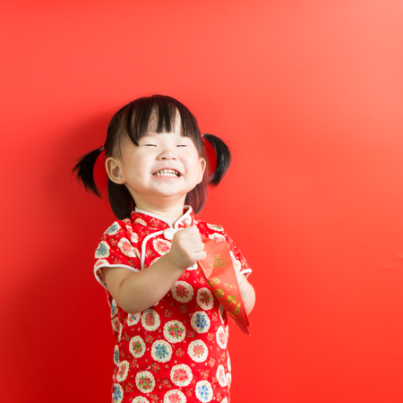 Little Asian girl holding red envelope on red background Stock Photo - 93369049