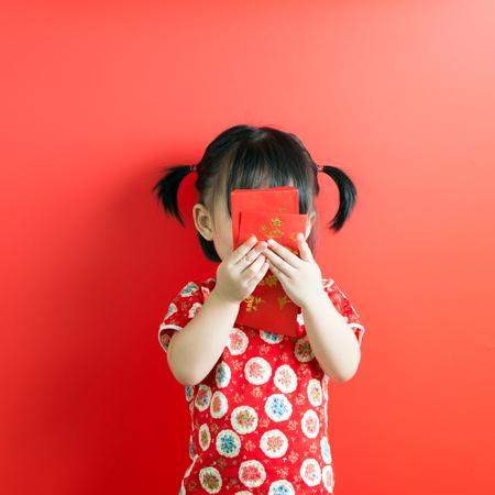 赤い背景に赤い封筒を持つ小さなアジアの女の子 写真素材 - 93215259