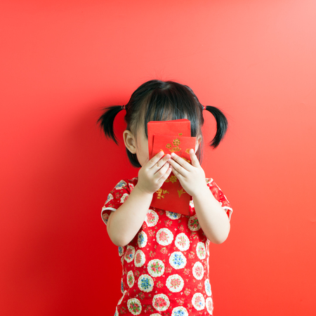 Little Asian girl holding red envelope on red background Reklamní fotografie - 93215259