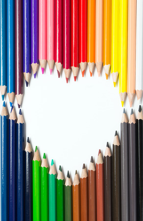 Color pencils arranged in a heart shape on white background