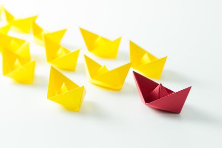 Leadership concept with a red paper ship leading among yelllow ships Stockfoto