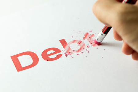 Close up of red pencil erasing the word debt on paper