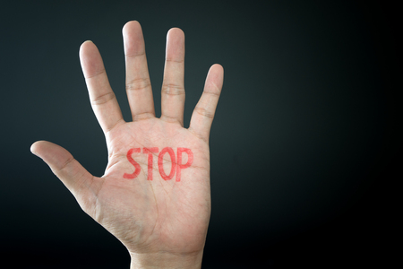 Hand with stop sign isolated on black background
