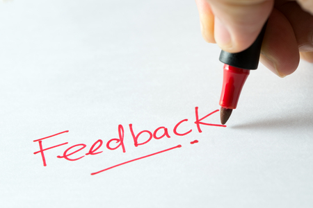 Hand writing feedback word or text with red marker pen isolated on white background