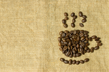Coffee cup symbol from coffee beans on gunny bag texture