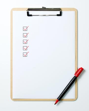Lista di controllo sulla lavagna per appunti con una penna rossa isolata su fondo bianco Archivio Fotografico