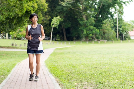 Front view of senior Asian woman jogging through park 스톡 콘텐츠