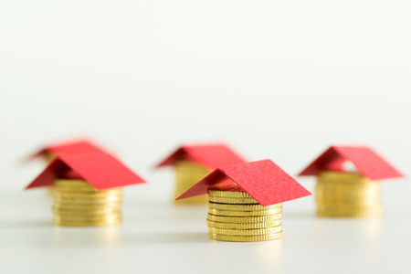 Houses made from lot of coins and a red color paper roof