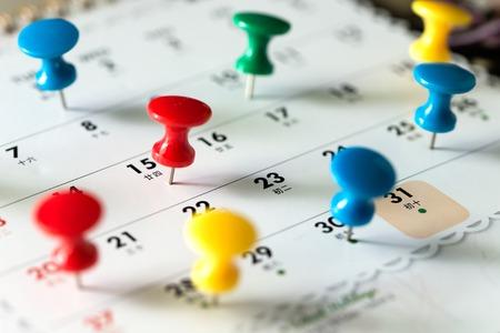 Différentes épingles de punaise de couleur sur le calendrier comme rappel