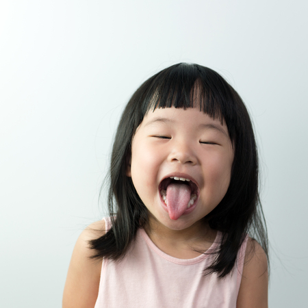 Happy little asian girl with funny face isolated on white background