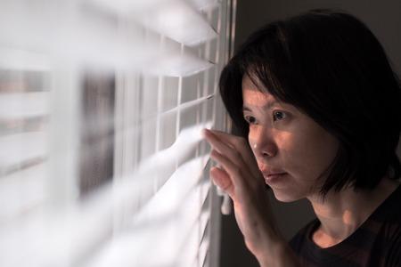 Portret van jonge Aziatische dame die uit venster gluren Stockfoto