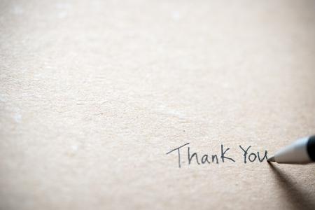 Escritura a mano gracias en un trozo de papel viejo grunge Foto de archivo