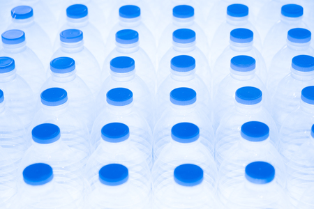 Overhead view on rows of mineral water plastic bottles in white