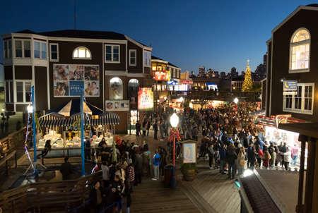 San Francisco, US - NOV 24, 2018: Visitors walk on Pier 39 stores and restaurants in evening at Fishermans wharf, San Franscisco.