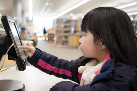 Asian young toddler using digital tablet in library