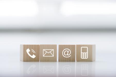 Neem contact met ons op concept met houtblok symbool telefoon, post, adres en mobiele telefoon. Website pagina contact met ons op of e-mail marketing concept