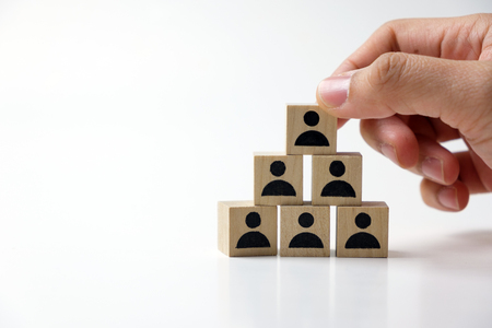Business man stacking wooden team blocks at table for team management concept or human resource planning Banque d'images