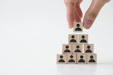 Business man stacking wooden team blocks at table for team management concept or human resource planning Reklamní fotografie