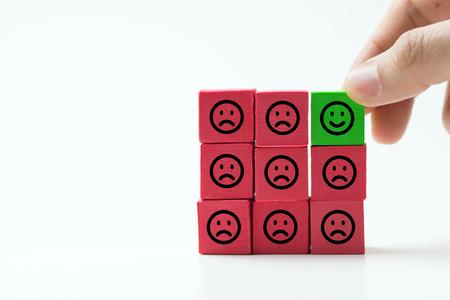 Einzelner grüner Smiley glücklicher Würfel unter vielen traurigen roten anderen Würfeln als Konzept für einzigartiges, optimistisches, Glück, Unterschied.