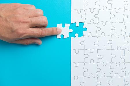 Legen Sie das letzte weiße Puzzleteil von Hand auf blauen Hintergrund und platzieren Sie es für Ihren Inhalt
